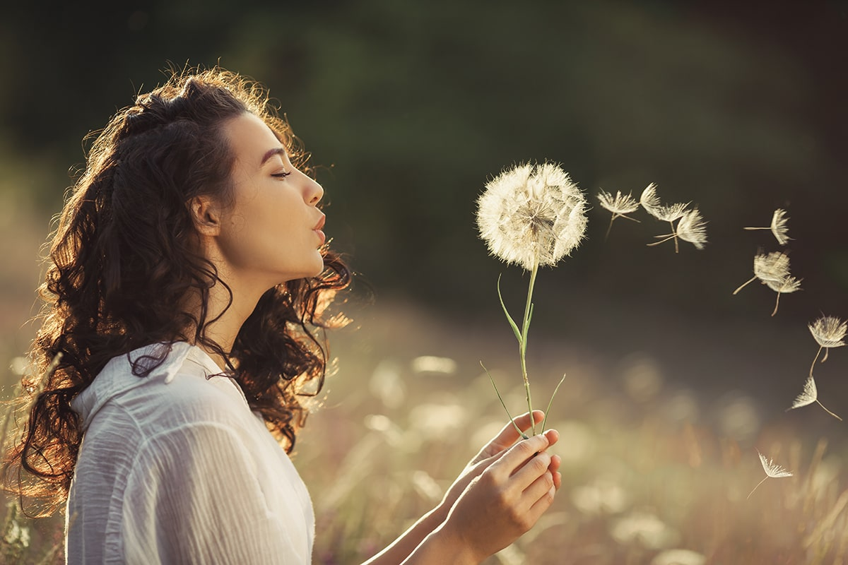 Woman blowing dandelion seeds