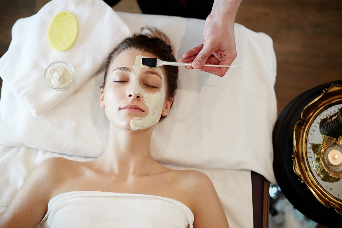 woman getting skin care mask at spa