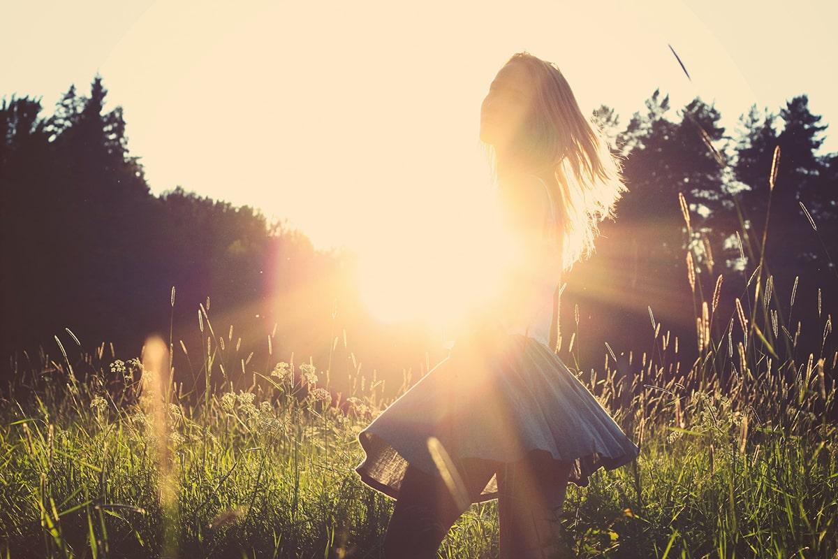 Woman in a field in front of sun
